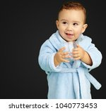 portrait of baby boy holding a... | Shutterstock . vector #1040773453