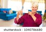 old woman showing  paper  indoor | Shutterstock . vector #1040786680