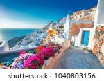 Santorini, Greece. Picturesq view of traditional cycladic Santorini houses on small street with flowers in foreground. Location: Oia village, Santorini, Greece. Vacations background.