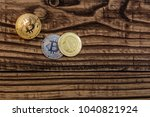 Small photo of golden and silver bitcoins lie ion wooden background