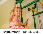 Small photo of little sisters girl in pink dress playing in the nursery, older sister made horns younger sister.