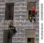 two firefighter climbing a wall ... | Shutterstock . vector #1040854600