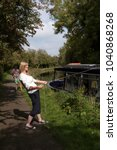 Small photo of Holidaymaker standing on towpath pulling the mooring line of a narrowboat during a holiday afloat