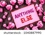 Small photo of Handwriting text showing Anything Else. Business photo showcasing Ask Asking Question to Have Answer written Pink Sticky Note Paper Folded Paper wooden background