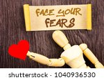 Small photo of Text sign showing Face Your Fears. Conceptual photo Challenge Fear Fourage Confidence Brave Bravery written Sticky Note Love Heart Holding By Sculpture the wooden background.