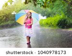 kid playing out in the rain.... | Shutterstock . vector #1040978173