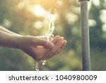 water from tap to woman hand in ... | Shutterstock . vector #1040980009