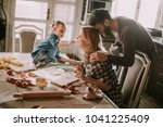 happy family making pasta in... | Shutterstock . vector #1041225409