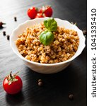 Small photo of Buckwheat porridge kasha in a bowl on dark wooden background