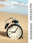 Small photo of closeup of an alarm on the sand of the beach, adjusting the time forward or backward one hour, at the beginning or at the end of the daylight savings time