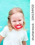 Adorable little girl holding lips party accessory - stock photo