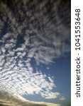 Small photo of Texture of altocumulus shape clouds at sky on sunset.Vertical image.