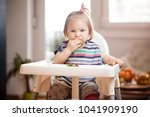 Stock photo little caucasian baby girl eating vegetables in a feeder with a excuse me hiccuping look on her 1041909190