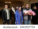 Small photo of Christening for baby in a rural church. Next of kin, woman and man standing with a baby on hands and waiting for ceremony. January 7, 2018. Bucha village, Ukraine