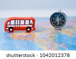 wooden red bus and compass on... | Shutterstock . vector #1042012378