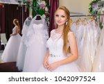 female trying on wedding dress...   Shutterstock . vector #1042097524