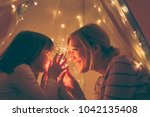 mother and daughter sitting in... | Shutterstock . vector #1042135408
