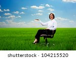 woman sitting in the armchair at the field and holding something at her hand - stock photo