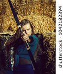 Small photo of woman, archer or hunter, with long hair shooting with bow and arrow on sunny day at archery target on hay bales. Concentrate, accuracy, ambition