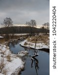 Small photo of A river writhe among meadows covered with snow