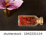 dried saffron spice in a bottle ... | Shutterstock . vector #1042231114