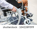 a young man in a wheelchair who ... | Shutterstock . vector #1042289599