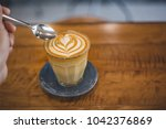 a cup of coffee latte on wood... | Shutterstock . vector #1042376869