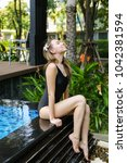 Small photo of young fit woman female relax close to swimming pool, enjoy weather in tropical country on background of apartment building on sunny day with sunshine. Concept of enjoying life, tratement for healthy