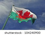 The Welsh Flag Against A Blue...