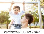 father with son training on... | Shutterstock . vector #1042527034