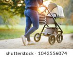 Woman With Baby Stroller Walks...