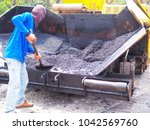 worker is using shovel scoop... | Shutterstock . vector #1042569760