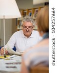 Retired senior people, old man reading news and magazines with wife in library - stock photo