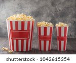 popcorn in three striped... | Shutterstock . vector #1042615354