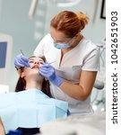 female dentist checking patient ... | Shutterstock . vector #1042651903