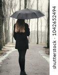a girl with an umbrella walking ... | Shutterstock . vector #1042652494