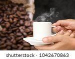 man hand holding white coffee... | Shutterstock . vector #1042670863