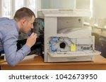 young male technician repairing ... | Shutterstock . vector #1042673950