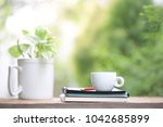 white cup with green plant at... | Shutterstock . vector #1042685899