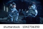 two astronauts collect rock and ... | Shutterstock . vector #1042736350
