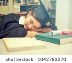 Small photo of Young asian female student holding book and wearing academic costume in library,education, happiness, graduation and people concept.