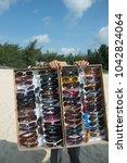 sunglasses seller on the beach... | Shutterstock . vector #1042824064