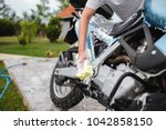 a man cleaning motorcycle with... | Shutterstock . vector #1042858150