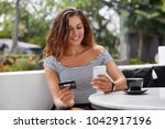 Small photo of Good looking brunette female in fashionable t shirt uses online banking on smart phone to transfer money from credit card, connected to free wifi in coffee shop. People and ecommerce concept