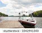 A wakeboard boat at a wooden dock in the Muskokas on a sunny day.