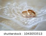 two wedding rings on a textured ... | Shutterstock . vector #1043053513