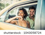 Small photo of Interracial couple driving on a taxi in Manhattan - Tourists sightseeing New York on a yellow cab