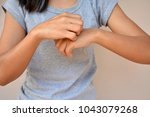 woman with itchy skin problem | Shutterstock . vector #1043079268