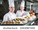 portrait of a chef with cooked... | Shutterstock . vector #1043087440