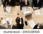two businesswomen shake hands... | Shutterstock . vector #1043108560